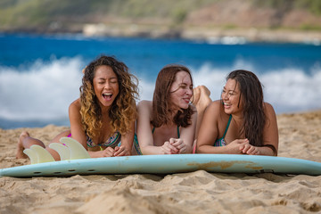 Surfer girls having fun with surfboard on a beach