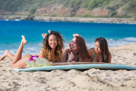 Surfer girls having fun with surfboard on a beach