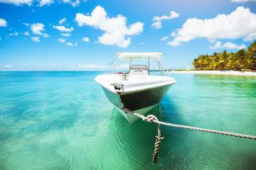 Stunning view of tropical beach with white yacht on pier.