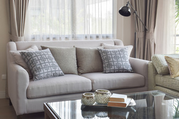 Books on glass top table and gray tone sofa set in modern living room
