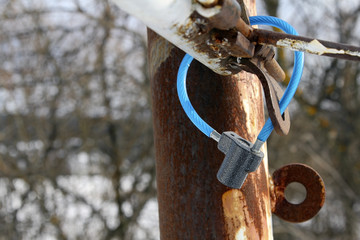 Modern padlock on rusty tube of fence