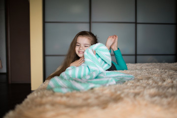 girl lying on the bed. The child hid under the blanket.