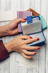 Women's hands, red nails, multi-colored business card holders