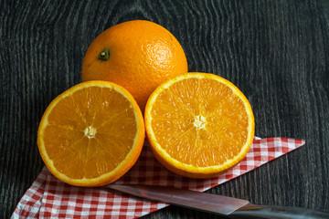Oranges sur fond noir coupée de moitié avec couteau et serviette