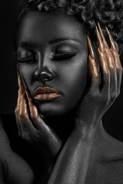 girl covered with black paint with gold lips and gold at your fingertips