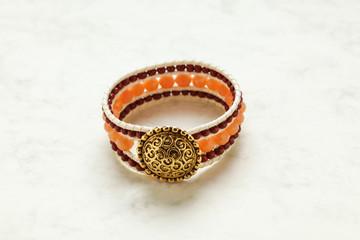 Handmade bracelet close up at marble stone pattern cardboard; no people,
