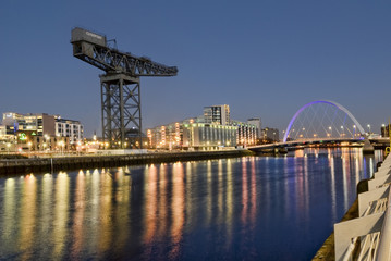 View over River Clyde in central Glasgow including office buildings , the Finnieston Crane, and the Clyde Arc Bridge.