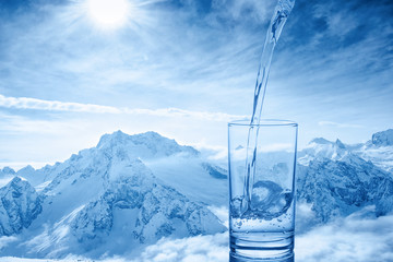 beautiful background of pouring blue water in transparent glass over winter landscape of mountains higher than clouds, close up