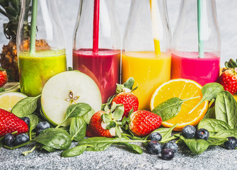 Various colorful beverage in bottles with fresh organic ingredients .Healthy smoothies or juice with fresh fruits, berries and vegetables, front view