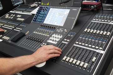 Hand operating sound system at concert.