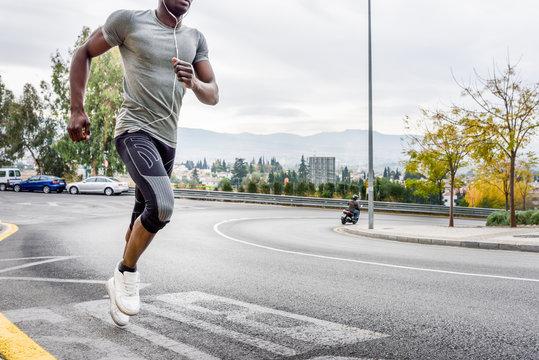 Black man running outdoors in urban road.