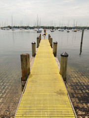 woman doing yoga on a yellow pier