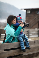 Kid taking a photo with mother holding him in arms