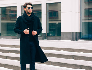 Elegant young handsome business man wearing suit and black coat posing against the background a business building. Fashion and Style. Streetstyle.