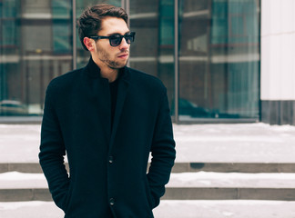 Portrait of young trendy man wearing a black coat with a raised collar. Street style. On the background a business building. Fashion.
