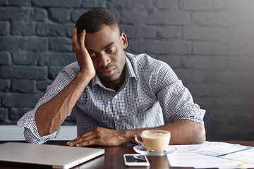 Frustrated tired young African-American employee touching his head, feeling absolutely exhausted because of overwork, calculating accounts, drinking another cup of coffee. Deadline and overwork Wall mural