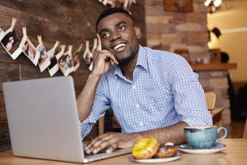 Cheerful young African student in formal shirt thinking what to comment on beautiful girl's picture on social media, looking up with pensive smile, sitting at cafe table in front of open laptop pc