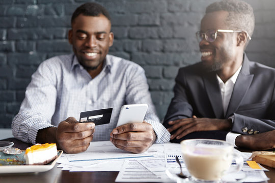 Successful happy African-American businessman paying bill with credit card online via internet, making transaction, using mobile bank application on cell phone during meeting with his partner at cafe