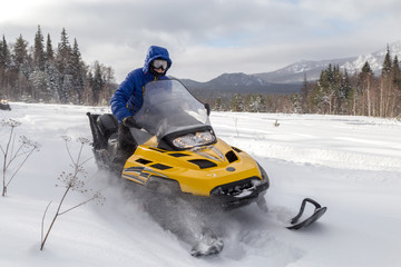 Woman on a snowmobile moving in a winter forest in the mountains of the Southern Urals.