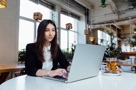 Young business woman sitting at table in cafe. Working with the notebook and glass of tea.