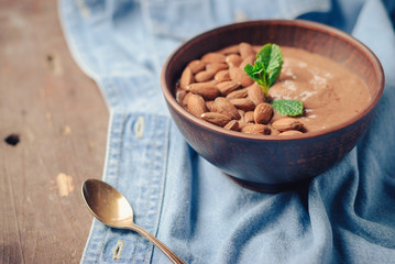 freshly made organic chocolate cream smoothie of banana and cocoa, decorated with almonds and mint leaf on a blue denim background. toned picture. close up and selective focus