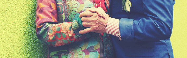 Elderly man passionately in love is explained by an elderly lady on a green wall. Love and passion.