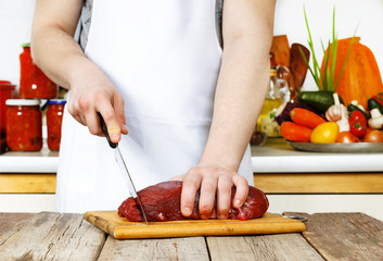 Young man cuts a meat on a cutting board in a domestic kitchen