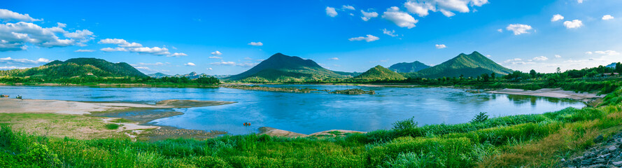 Panorama view of mountain full of green tree with river in front and clear blue sky.