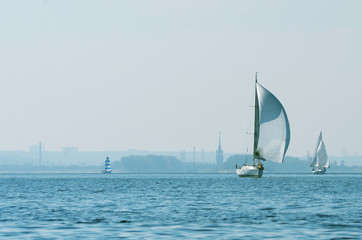 Sailing boats on the river, the reflection on water in the distance shore.