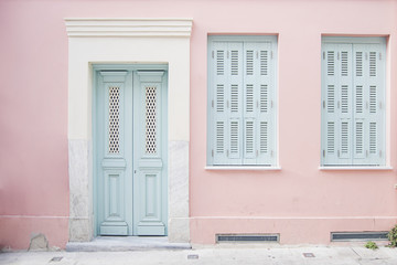 Pastel pink building and pale blue doorway surrounded by marble in Athens, Greece