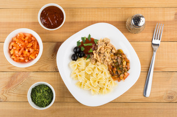 Plate with pasta, chicken meat, ketchup, greens, olives, peper