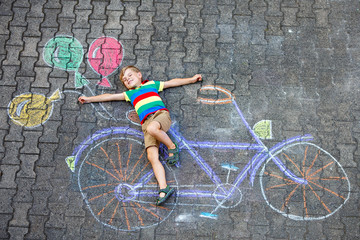 little kid boy having fun with bicycle chalks picture on ground