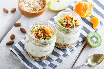 Healthy homemade granola with yogurt and fruits in a rustic jar. Traditional American food on a table. Classic snack. Top view.