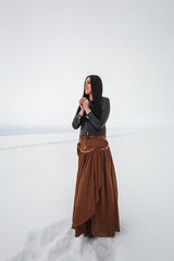 Girl in ethnic costume standing in a field, which is covered with snow