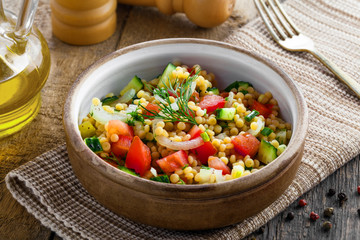 Couscous with tomatoes, cucumber and onion in a bowl for healthy breakfast. Traditional Israeli food Ptitim with vegetables. Moroccan cuisine meal.