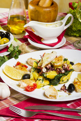 Grilled calamari on a white plate with boiled potatoes and chard, lemon, cherry tomatoes and olives.