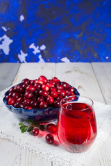 Red cranberry juice in a glass, cranberries in the blue clay bowl on the table