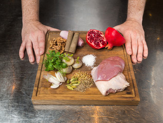 A cutting board with ingredients for a pomegranate duck dish. The ingredients include, Free range duck breast fillets, herbs and spices, shallots, pomegranate, cinnamon, walnuts and ground sea salt.