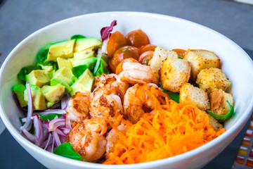 Shrimp salad with abocado in a white bowl