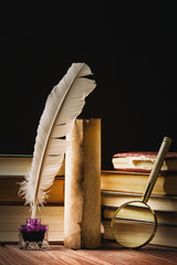 Literature concept. Inkstand with feather near magnifying glass and old scroll