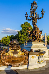 Fototapete - Pont Alexandre III, the lantern with statues of Nymphs, in Paris