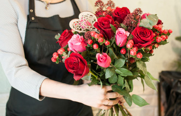 Girl collects a florist bouquet of roses. Wedding preparations. Workplace