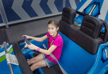 Child enjoying a day at the amusement park. Sitting in an automobile theme park ride ready to go on a warm summer day outdoors. Smiling and having fun and ready to go on a ride