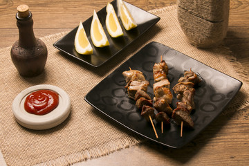 Plate of shish kebab grilled on wooden skewers