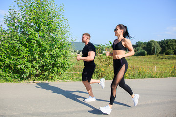 Couple of strong fit man and woman jogging outdoors