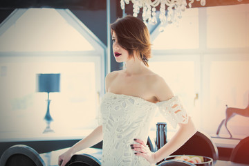 beautiful young woman standing near the table in the luxury room and looking somewhere