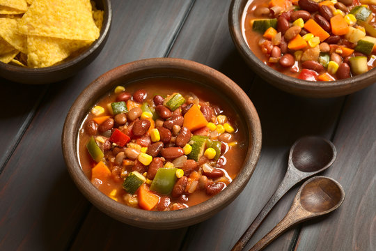 Vegetarian chili dish made with kidney bean, carrot, zucchini, bell pepper, sweet corn, tomato, onion, garlic, photographed with natural light (Selective Focus, Focus in the middle of the first dish)