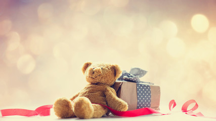 cute teddy bear, red ribbon and beautiful gift on the fairy lights bokeh background