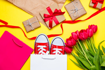 bunch of red tulips, red gumshoes, cool shopping bags, things for wrapping and beautiful gifts on the wonderful yellow background