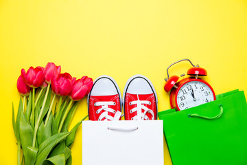 bunch of red tulips, red gumshoes, cool shopping bags and alarm clock on the wonderful yellow background
